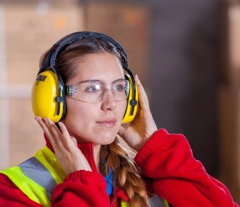 Kobieta z ochronnikami słuchu na głowie